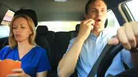 Η οδήγηση ζεύγους στο αυτοκίνητο, ένας άνδρας και μια γυναίκα οδηγούν μαζί στο αυτοκίνητο μέσω των οδών της πόλης και κοιτάζουν γ απόθεμα βίντεο