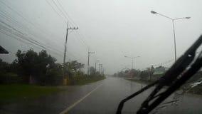 Η οδική άποψη μέσω του ανεμοφράκτη αυτοκινήτων με τη βροχή μειώνεται, περιμένοντας το σταυρό το δρόμο απόθεμα βίντεο