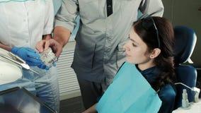 Η οδοντιατρική, βοηθός παρουσιάζει στο υπομονετικό πλαστό σαγόνι, εξηγεί στην κλινική φιλμ μικρού μήκους