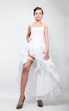 Η ολόκληρη νύφη σε ένα γαμήλιο φόρεμα και ένα νυφικό hairdo, ανύψωσε hem του φορέματός της εύθυμη νύφη πρόκλησης Στοκ Φωτογραφίες