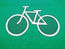 Η πάροδος ποδηλάτων υπογράφει το άσπρο χρώμα στο πράσινο υπόβαθρο χρώματος σταθμεύει δημόσια Στοκ Εικόνες