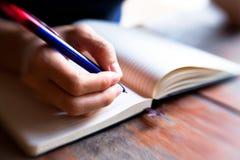 Η πέννα χεριών γράφει σε ένα σημειωματάριο Στοκ εικόνες με δικαίωμα ελεύθερης χρήσης