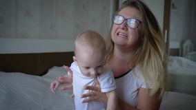 Η πίεση, νευρική μητέρα eyeglasses ανυψώνει συχνά το νήπιο στα χέρια που κάθεται στο κρεβάτι απόθεμα βίντεο