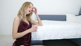Η πίεση, όμορφη νέα ανύπαντρη στα nightdress πίνει τη σαμπάνια καθμένος στο πάτωμα κοντά στο κρεβάτι απόθεμα βίντεο