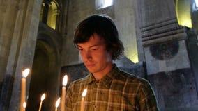Η πίστη του ατόμου βάζει ένα κερί και προσεύχεται πριν από ένα εικονίδιο στην ορθόδοξη καθολική εκκλησία απόθεμα βίντεο