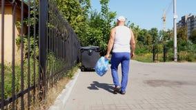 Η πίσω άποψη, άτομο φέρνει μια συσκευασία των απορριμάτων στα χέρια του, παίρνει έξω τα απορρίμματα Θερινή καυτή ημέρα Οικολογία  απόθεμα βίντεο