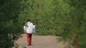 Η πίσω άποψη από το copter στο χαμένο ταξιδιώτη που προσπαθεί να βρεί το δρόμο που χρησιμοποιεί το χάρτη Δασική θέση απόθεμα βίντεο