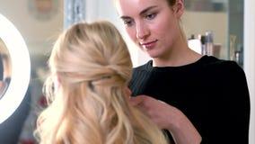 Η πίσω άποψη επαγγελματική να κάνει καλλιτεχνών makeup αποζημιώνει την ξανθή γυναίκα απόθεμα βίντεο