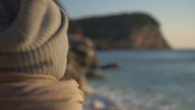 Η πίσω άποψη, κορίτσι σε ένα καπέλο εξετάζει παλιρροιακό άντεξε στο ηλιοβασίλεμα απόθεμα βίντεο