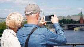 Η πίσω άποψη της ανώτερης στάσης ζευγών στη γέφυρα παρατήρησης παίρνει τις φωτογραφίες τουριστών της πόλης στο κινητό τηλέφωνο απόθεμα βίντεο