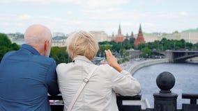 Η πίσω άποψη της ανώτερης στάσης ζευγών στη γέφυρα παρατήρησης κοιτάζει γύρω από την πόλη Οι συνταξιούχοι ταξιδεύουν στη Ρωσία απόθεμα βίντεο