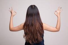 Η πίσω άποψη της ασιατικής γυναίκας παρουσιάζει διπλό ΕΝΤΑΞΕΙ σημάδι χεριών Στοκ Εικόνες