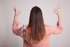 Η πίσω άποψη της ασιατικής γυναίκας παρουσιάζει διπλό ΕΝΤΑΞΕΙ σημάδι χεριών Στοκ Φωτογραφία