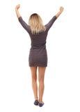 Η πίσω άποψη της γυναίκας αυξάνει τα χέρια σας εκφράζοντας επάνω τη χαρά Στοκ Φωτογραφίες