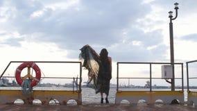 Η πίσω άποψη της γυναίκας που κρατά την άκρη του μακριού φορέματος και που προσέχει το ηλιοβασίλεμα της αποβάθρας φιλμ μικρού μήκους