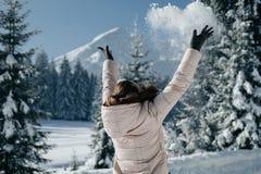 Η πίσω άποψη της γυναίκας σε ένα χειμερινό μπεζ σακάκι ρίχνει το χιόνι στο β στοκ εικόνες