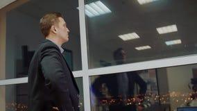 Η πίσω άποψη του αρσενικού επιχειρηματία έντυσε στο εταιρικό κοστούμι κοιτάζοντας από το παράθυρο περιμένοντας το συνέταιρο σε σύ φιλμ μικρού μήκους