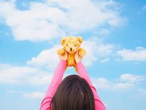 Η πίσω άποψη του ασιατικού κοριτσιού που κρατά teddy αντέχει το παιχνίδι πέρα από το μπλε ουρανό Στοκ εικόνα με δικαίωμα ελεύθερης χρήσης
