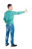 Η πίσω άποψη του ατόμου στο πουκάμισο παρουσιάζει αντίχειρες Στοκ Εικόνα