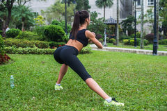 Η πίσω άποψη του κατάλληλου κοριτσιού που κάνει δευτερεύον lunge ασκεί υπαίθρια Στοκ Εικόνες