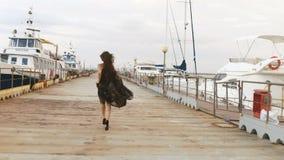 Η πίσω άποψη του κοριτσιού στο μακρύ φόρεμα που τρέχει μέσω της αποβάθρας απόθεμα βίντεο