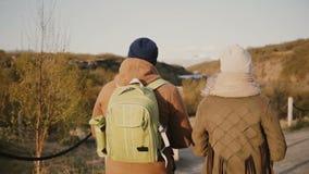 Η πίσω άποψη του νέου ζεύγους έχει μια ρομαντική ημερομηνία στη φύση Διακινούμενοι άνδρας και γυναίκα που στην κοιλάδα βουνών, φιλμ μικρού μήκους