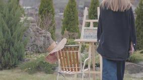 Η πίσω άποψη του ψηλού ζωγράφου νέων κοριτσιών έρχεται και κάθεται μπροστά από ξύλινο easel να σύρει μια εικόνα Η κυρία καπνίζει φιλμ μικρού μήκους