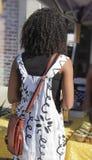 Η πίσω άποψη του unrecognizable κοριτσιού αφροαμερικάνων σε ένα χαριτωμένο φόρεμα με το πορτοφόλι που στέκεται στους προμηθευτές  στοκ εικόνες