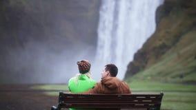 Η πίσω άποψη των νέων τουριστών συνδέει τη στήριξη κοντά στον καταρράκτη Skogafoss στην Ισλανδία Άνδρας και γυναίκα στον πάγκο απόθεμα βίντεο