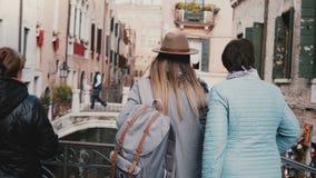 Η πίσω νέα κόρη άποψης και η ανώτερη μητέρα στέκονται μαζί στη γέφυρα καναλιών απολαμβάνοντας τη θέα σχετικά με τις διακοπές στη  απόθεμα βίντεο