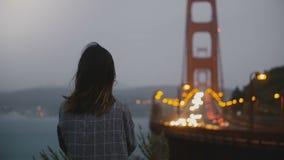 Η πίσω νέα χαλαρωμένη γυναίκα άποψης που προσέχει την εικονική χρυσή γέφυρα πυλών bokeh εμπορεύεται την άποψη στο σκοτεινό βράδυ  απόθεμα βίντεο