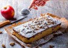 Η πίτα, που ξεσκονίζονται τον ξινό με την κονιοποιημένη ζάχαρη και το χέρι της Apple ψεκάζουν Στοκ εικόνες με δικαίωμα ελεύθερης χρήσης