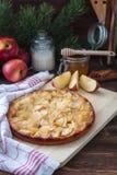 Η πίτα της Apple με μια πετσέτα κουζινών, ένα μέλι, μια κανέλα και fir-tree διακλαδίζεται στο ξύλινο υπόβαθρο Στοκ φωτογραφία με δικαίωμα ελεύθερης χρήσης