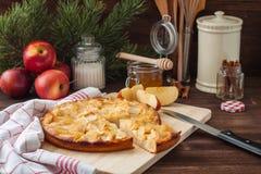 Η πίτα της Apple με μια πετσέτα κουζινών, ένα μέλι, μια κανέλα και fir-tree διακλαδίζεται στο ξύλινο υπόβαθρο Στοκ εικόνα με δικαίωμα ελεύθερης χρήσης