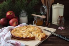 Η πίτα της Apple με μια πετσέτα κουζινών, ένα μέλι, μια κανέλα και fir-tree διακλαδίζεται στο ξύλινο υπόβαθρο Στοκ φωτογραφίες με δικαίωμα ελεύθερης χρήσης