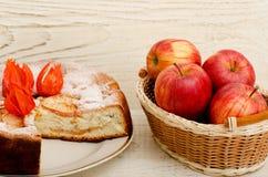 Η πίτα της Apple, Physalis ανθίζει και ώριμα μήλα σε έναν ελαφρύ ξύλινο πίνακα Στοκ εικόνα με δικαίωμα ελεύθερης χρήσης