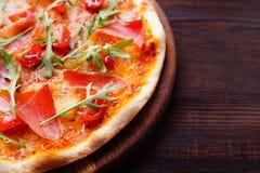 Η πίτσα ζαμπόν με το επίπεδο arugula βάζει με το διάστημα αντιγράφων Στοκ Εικόνες