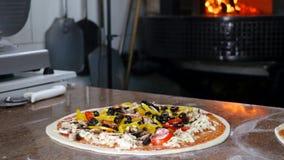 Η πίτσα καρυκευμάτων αρχιμαγείρων με τα φρέσκα καλύμματα, κλείνει επάνω, σε αργή κίνηση Στοκ Εικόνες