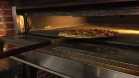 Η πίτσα τοποθετείται στο φούρνο απόθεμα βίντεο