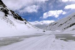 Η παγωμένη λίμνη και τα χιονώδη βουνά Στοκ Φωτογραφία