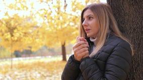 Η παγωμένη στάση γυναικών στην οδό φθινοπώρου στο δέντρο θερμαίνει την αναπνοή χεριών της απόθεμα βίντεο