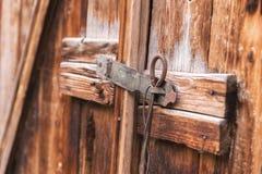 Η παλαιά απλή κλειδαριά σε μια ξύλινη πόρτα έκλεισε με έναν αγροτικό σύρτη καρφιτσών μετάλλων σε μια παλαιά πόρτα φιαγμένη από ξύ Στοκ Εικόνα