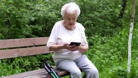 Η παλαιά γιαγιά εξετάζει το smartphone Διαδικτύου απόθεμα βίντεο