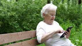 Η παλαιά γιαγιά εξετάζει το smartphone Διαδικτύου φιλμ μικρού μήκους