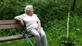 Η παλαιά γιαγιά κάθεται τη στήριξη σε έναν πάγκο πάρκων απόθεμα βίντεο
