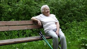 Η παλαιά γιαγιά κάθεται τη στήριξη σε έναν πάγκο πάρκων φιλμ μικρού μήκους