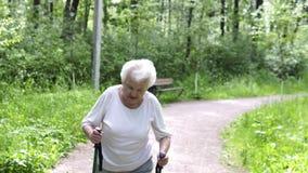 Η παλαιά γιαγιά πηγαίνει με τα ραβδιά για το περπάτημα στο δρόμο φιλμ μικρού μήκους