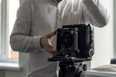Η παλαιά κάμερα σε ένα τρίποδο στέκεται σε ένα υπόβαθρο ενός τοίχου στοκ εικόνες με δικαίωμα ελεύθερης χρήσης