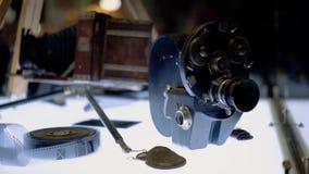 Η παλαιά κάμερα ταινιών και η ταινία είναι στον τονισμένο πίνακα φιλμ μικρού μήκους