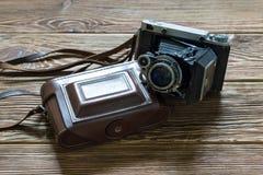 Η παλαιά μέση περίπτωση καμερών και δέρματος αποστασιομέτρων σχήματος Ξύλινη ανασκόπηση Στοκ φωτογραφία με δικαίωμα ελεύθερης χρήσης